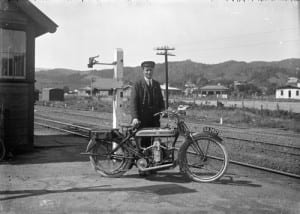 J McDonald standing behind a Douglas motorcycle at the Silverstream Railway Station.